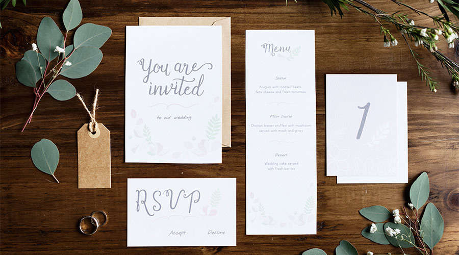 wedding invitations and menu on table