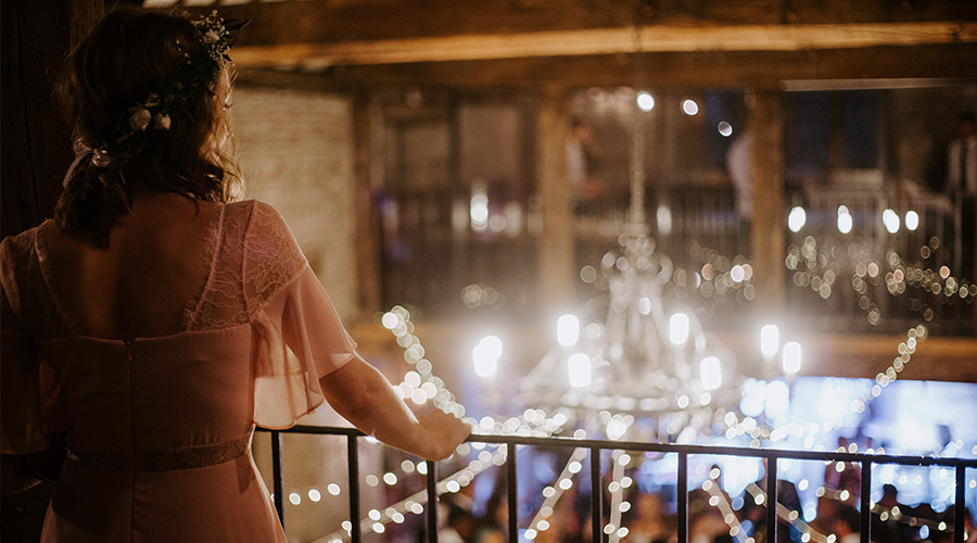 bride standing on balcony with wedding planner on wedding day at wedding venue