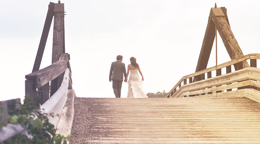 newlywed couple walking hand in hand across a bridge unity ceremony