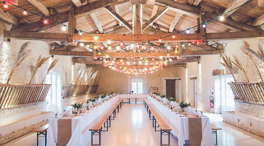 indoor wedding venue with long tables and lights