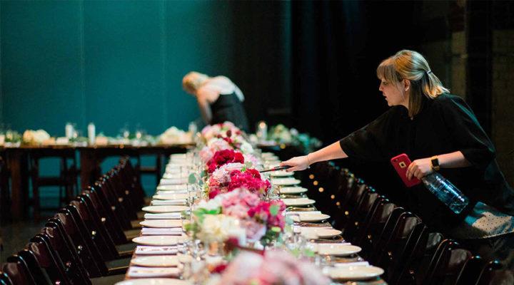 wedding coordinator setting up wedding table at a wedding venue