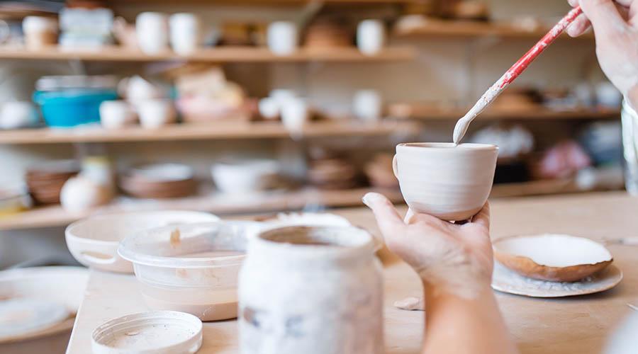 female potter painting a pot