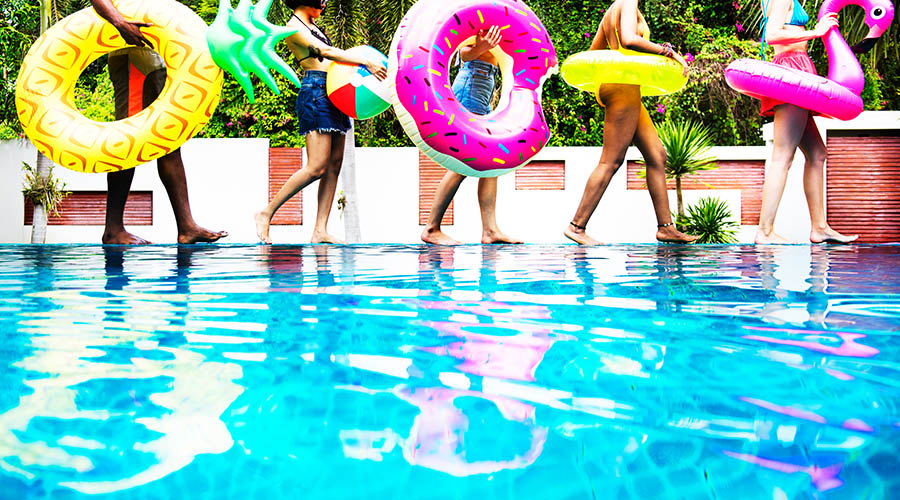 friends walking along poolside with inflatables