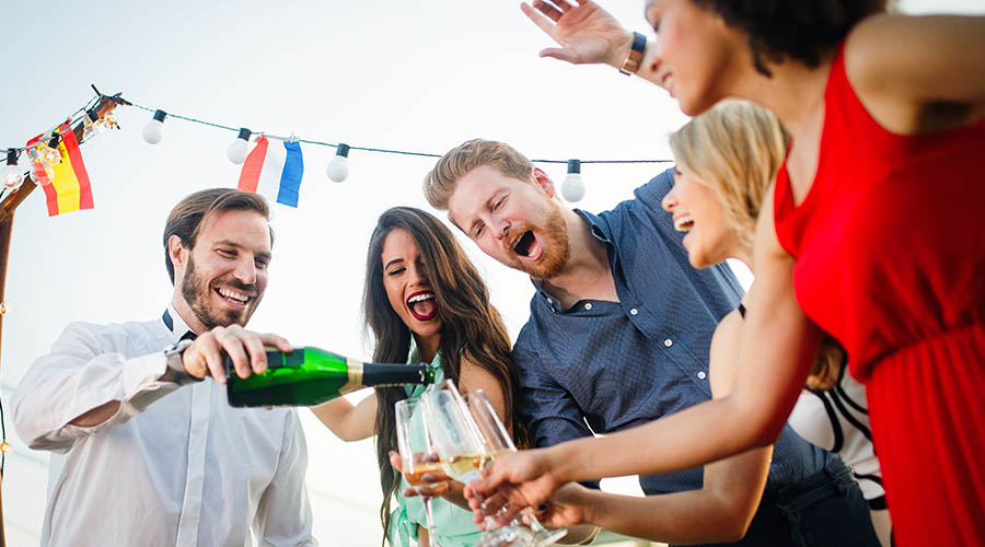 man pouring champagne for friends