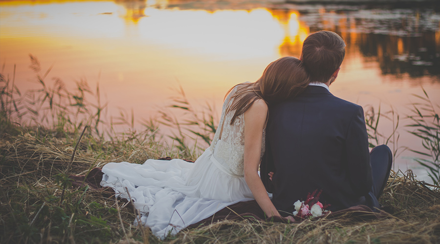 couple sitting by a lake on their wedding day
